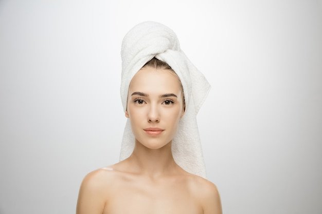 Journée de la beauté. femme portant une serviette isolée sur le mur blanc du studio.