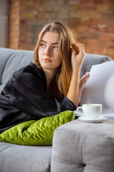Journée beauté pour vous-même. femme portant une robe de soie faisant sa routine quotidienne de soins de la peau à la maison. allongé sur un canapé, lisant des magazines, buvant du café. concept de beauté, soins personnels, cosmétiques, jeunesse. fermer.