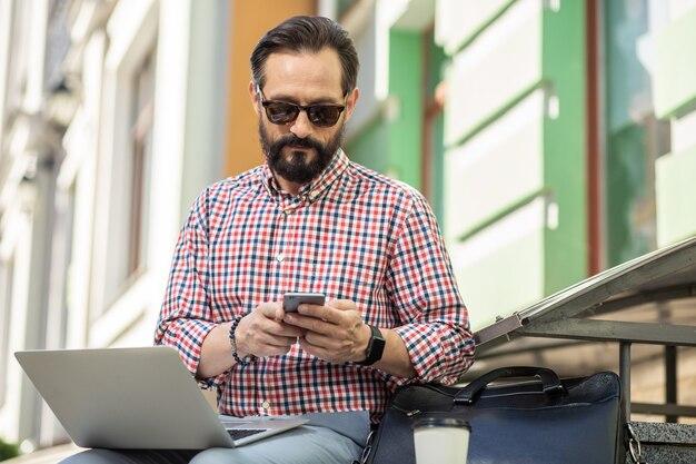 Journée chargée. agréable homme concentré à l'aide de son smartphone assis à l'extérieur