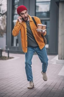 Journée chargée. jeune homme barbu dans un chapeau rouge, parler au téléphone et laisser tomber les tasses de café