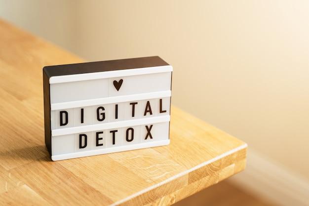 Journée de désintoxication numérique. lightbox sur une surface en bois et des murs blancs. interdiction des gadgets