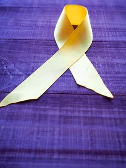Journée du cancer infantile. ruban jaune sur fond bleu