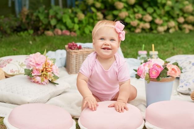 Journée des enfants, une fille dans le parc est assise dans un panier avec des macarons sur un pique-nique estival