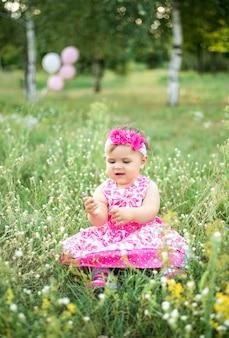 Journée des enfants, une fille dans le parc en été assis sur l'herbe