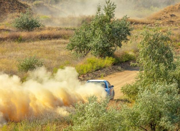 Journée ensoleillée d'été. piste de terre pour le rallye. une voiture roule dans un virage et fait beaucoup de poussière 05
