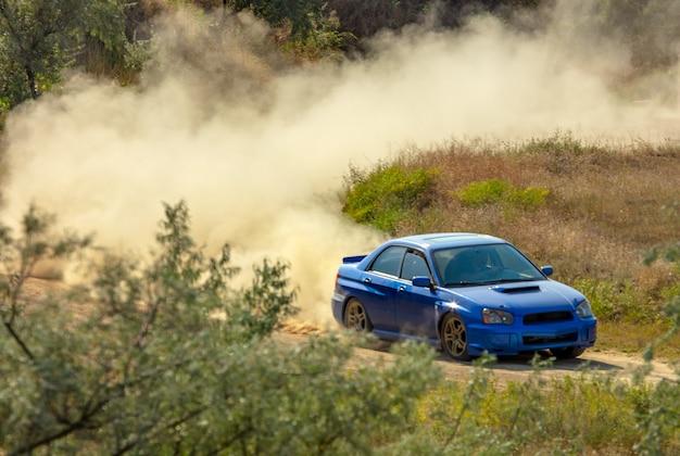 Journée ensoleillée d'été. piste de terre pour le rallye. une voiture roule dans un virage et fait beaucoup de poussière 06