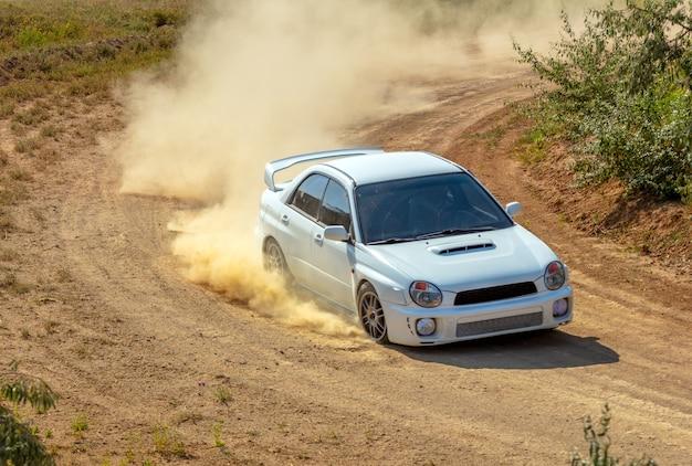 Journée ensoleillée d'été. piste de terre pour le rallye. une voiture roule dans un virage et fait beaucoup de poussière 07