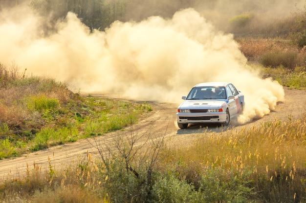 Journée ensoleillée d'été. piste de terre pour le rallye. une voiture traverse un virage et fait beaucoup de poussière 03