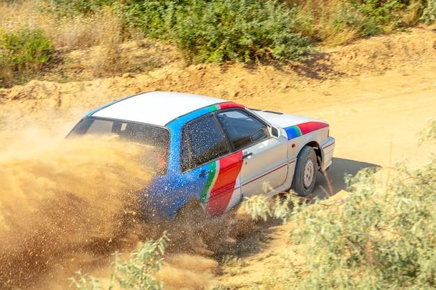 Journée ensoleillée d'été. piste de terre pour le rallye. une voiture traverse un virage et fait beaucoup de poussière 04