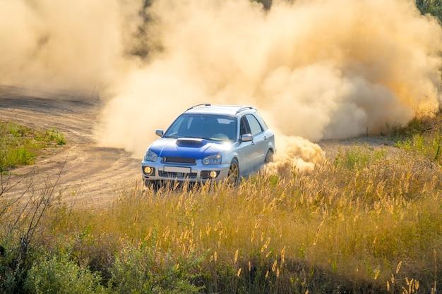 Journée ensoleillée d'été. la voiture bleue tourne le chemin de terre. beaucoup de poussière