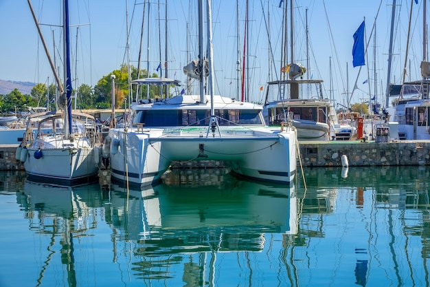 Journée ensoleillée à la marina. catamaran à voile et nombreux mâts d'autres yachts