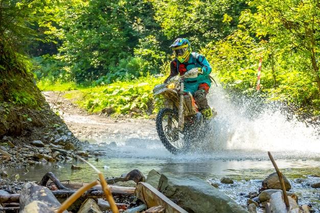 Journée d'été ensoleillée. l'athlète d'enduro surmonte un ruisseau forestier. beaucoup d'eau pulvérisée au soleil