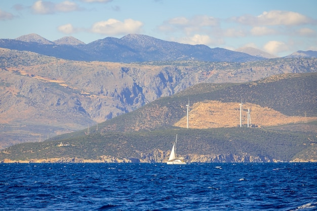 Journée d'été ensoleillée et côte vallonnée avec parcs éoliens. yacht à voile solitaire
