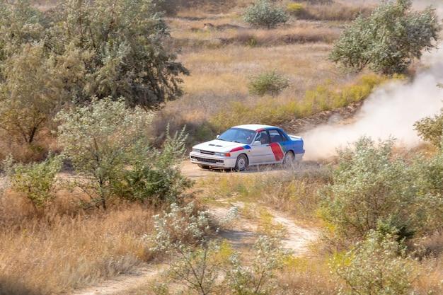 Journée d'été ensoleillée. piste de rallye poussiéreuse. la voiture de sport fait beaucoup de poussière à son tour 04