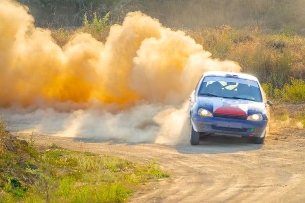 Journée d'été ensoleillée. la voiture de rallye tourne le chemin de terre. beaucoup de poussière