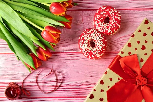 Journée de la femme, le 8 mars, beignets roses avec des fleurs sur une surface rose sous un arbre, boîte-cadeau, vue du dessus