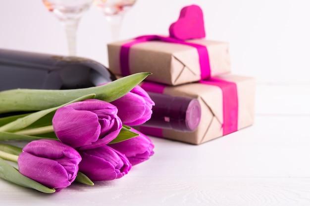 Journée de la femme. cadeaux avec fleurs et vin sur mur blanc