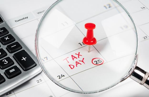 Journée fiscale écrite sur un calendrier avec une punaise rouge.