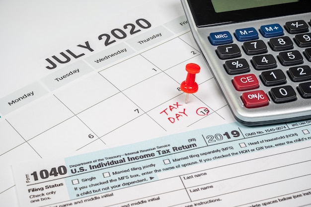La journée fiscale a été prolongée jusqu'au 15 juillet en raison de covid-19. calendrier de juillet montrant le formulaire de retour 1040 et le jour des impôts.