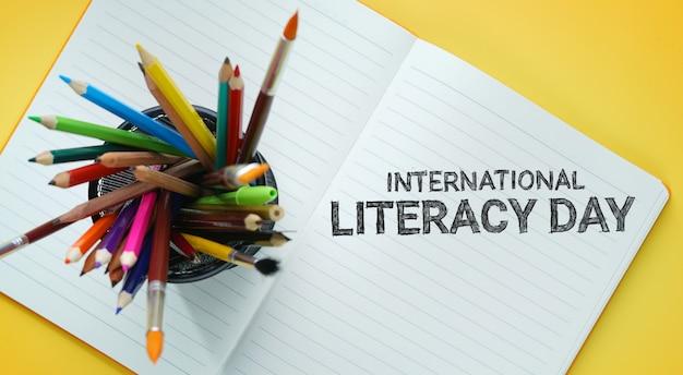 Journée internationale de l'alphabétisation. école stationnaire dans le panier sur livre ouvert vue de dessus fond jaune
