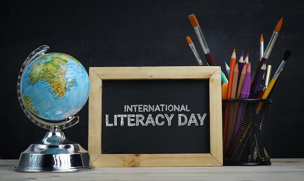 Journée internationale de l'alphabétisation. globe terrestre, fournitures scolaires et réveil