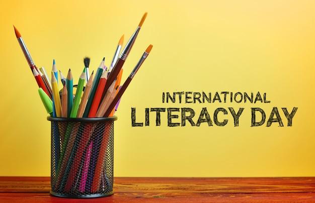 Journée internationale de l'alphabétisation. papeterie scolaire dans le panier sur la table en bois
