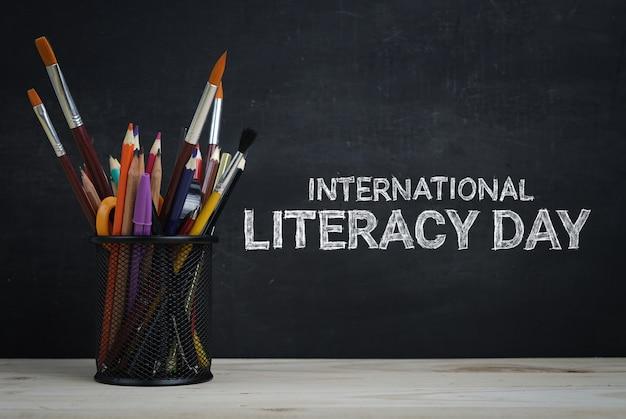 Journée internationale de l'alphabétisation. papeterie scolaire sur tableau noir