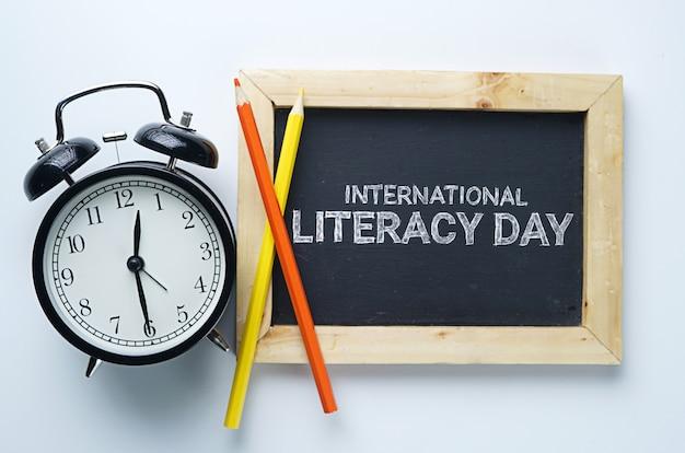 Journée internationale de l'alphabétisation. réveil, crayon de couleur et tableau noir sur fond blanc