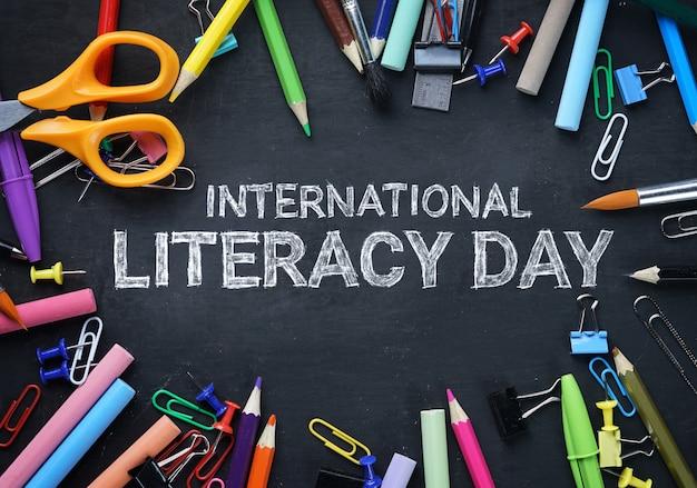 Journée internationale de l'alphabétisation. school stationary top view sur tableau noir