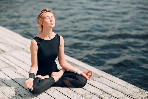 Journée internationale du yoga. jeune femme pratiquant le hatha yoga sur la côte du lac,