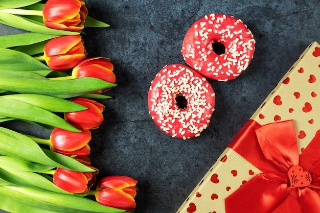 Journée internationale de la femme, 8 mars, fleurs tulipes avec beignets roses sur une surface sombre, vue de dessus, cadeau, flatley