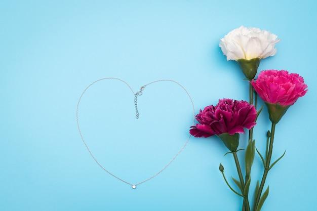 Journée internationale de la femme avec des fleurs et un collier en forme de coeur sur fond bleu