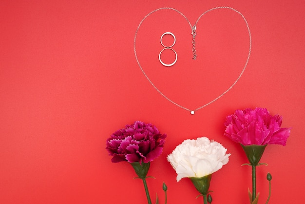 Journée internationale de la femme avec des fleurs et un collier en forme de coeur sur fond rouge
