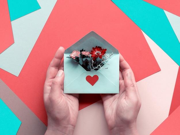 Journée internationale de remerciement. carte de voeux avec mains tenant une enveloppe avec des fleurs sur du papier en couches
