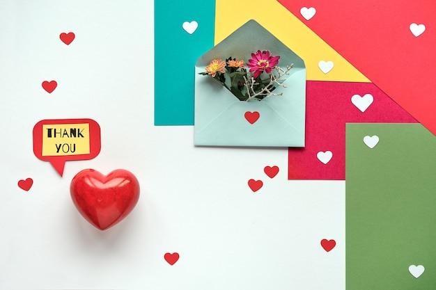 Journée internationale de remerciement. merci étiquette en papier, coeur en pierre et fleurs sur papier.