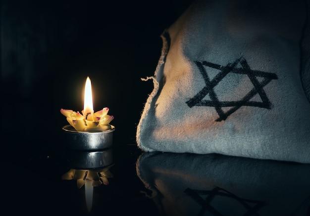 Journée de mémoire des victimes de l'holocauste brûlant dans la bougie nocturne et symbole de l'étoile juive de david