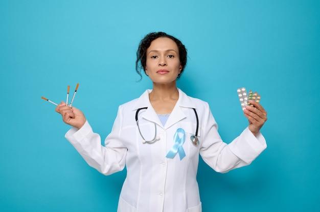 Journée mondiale du diabète. 14 novembre. une femme médecin en blouse médicale blanche portant un ruban de sensibilisation bleu tient des seringues à insuline, des comprimés pharmaceutiques sous blister, isolés sur fond bleu, espace pour copie