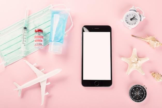 Journée mondiale du tourisme vue de dessus modèle avion masque médical vaccin contre le coronavirus et smartphone