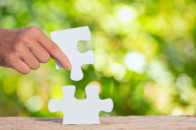 Journée mondiale de l'habitat, gros plan photo d'un morceau de puzzle blanc à la main