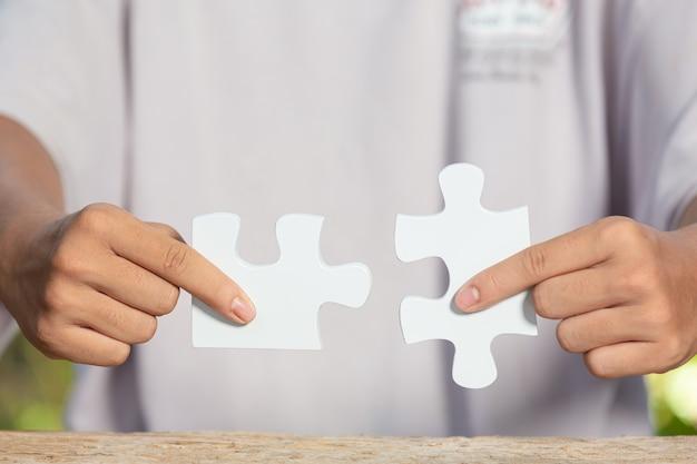 Journée mondiale de l'habitat, photo en gros plan d'un morceau de puzzle blanc dans chaque main