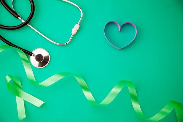 Journée mondiale de la santé. concept de soins de santé et de fond médical du stéthoscope avec ruban coeur sur fond de papier vert copie espace pour votre texte.