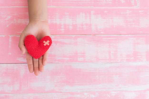 Journée mondiale de la santé, main d'enfant sur coeur rouge à la main sur fond en bois rose