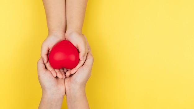 Journée mondiale de la santé, mains adultes et enfants tenant coeur rouge, soins de santé, amour et concept d'assurance famille