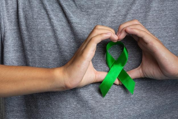 Journée mondiale de la santé mentale. la main de l'homme montrant en forme de coeur autour d'un ruban vert