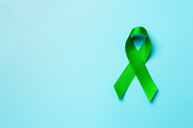 Journée mondiale de la santé mentale. ruban vert sur fond bleu