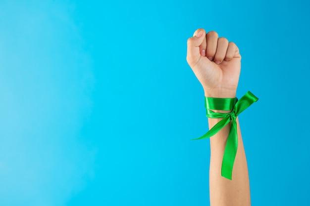 Journée mondiale de la santé mentale. rubans verts noués au poignet sur fond bleu