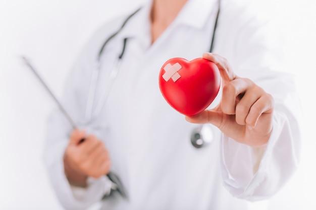 Journée mondiale de la santé, soins de santé et concept médical. femme médecin avec stéthoscope tenant coeur