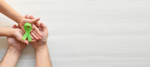 Journée mondiale de sensibilisation à la santé mentale mains d'adultes et d'enfants tenant un ruban vert sur fond blanc
