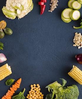 Journée mondiale végétalienne. cadre d'ingrédients végétariens frais pour la cuisson de la plaque végétalienne sur fond sombre vue de dessus