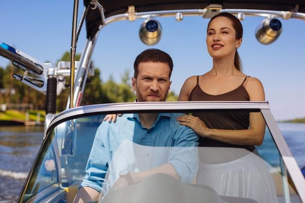 Journée paisible. agréable jeune couple naviguant sur un bateau ensemble et la femme posant ses mains sur les épaules de son mari